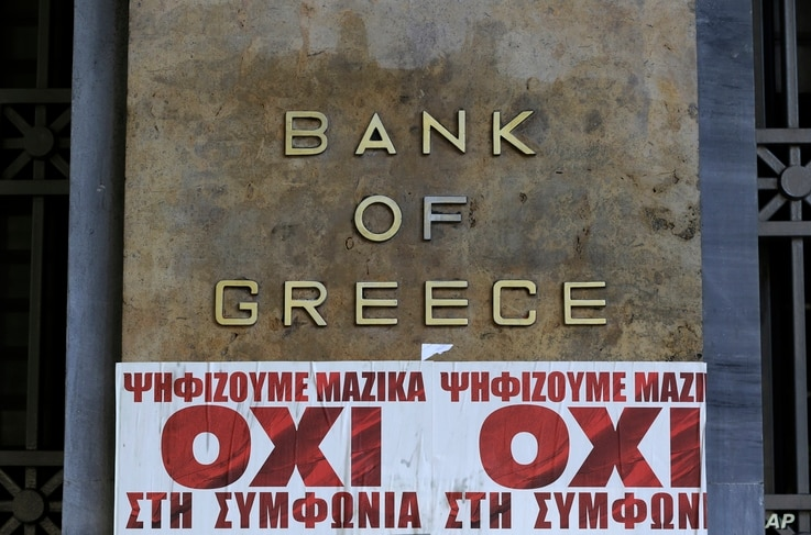 "Posters reading ""We vote en masse, no the agreement'' are seen under Bank of Greece logo in Athens, July 3, 2015."
