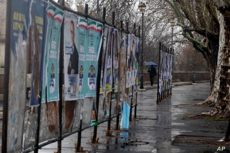 Torn electoral posters hang on billboard in Rome, March 5, 2018.
