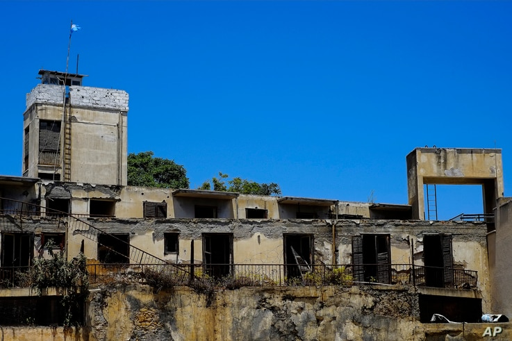 An abandoned building with a U.N guard post with a U.N flag on top in the U.N buffer zone that divides the Greek and Turkish Cypriots controlled areas in central divided capital Nicosia, Cyprus, Friday, June 30, 2017.