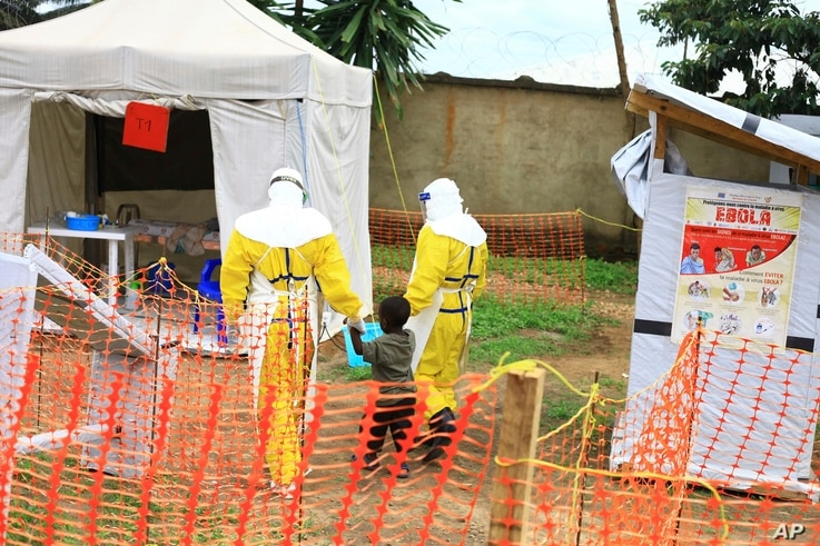 FILE - Health workers walk with a boy suspected of having been infected with the Ebola virus, at an Ebola treatment center in Beni, near Congo's border with Uganda, Sept. 9, 2018.