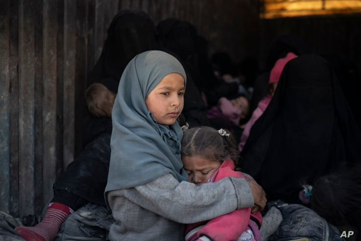 Children ride in the back of a truck that is part of a convoy evacuating hundreds out of the last territory held by Islamic State militants, in Baghuz, eastern Syria, Feb. 20, 2019.