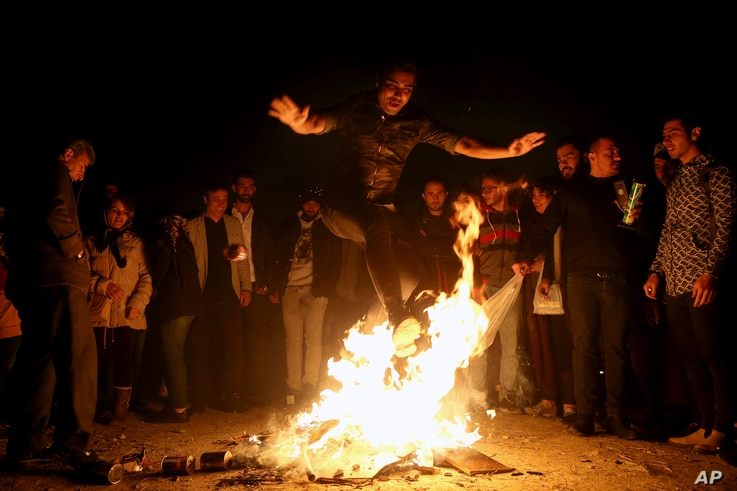 "An Iranian man jumps over a bonfire during a celebration, known as ""Chaharshanbe Souri,"" or Wednesday Feast, marking the eve of the last Wednesday of the solar Persian year, March 19, 2019 in Tehran."