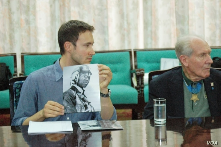 Military history author Adam Makos, seated next to Thomas Hudner, shows North Korean army officers a photo of US Navy pilot Jesse Brown who crash landed his plane in their country in 1950, in Pyongyang, July 22, 2013. (Photo: Steve Herman / VOA)