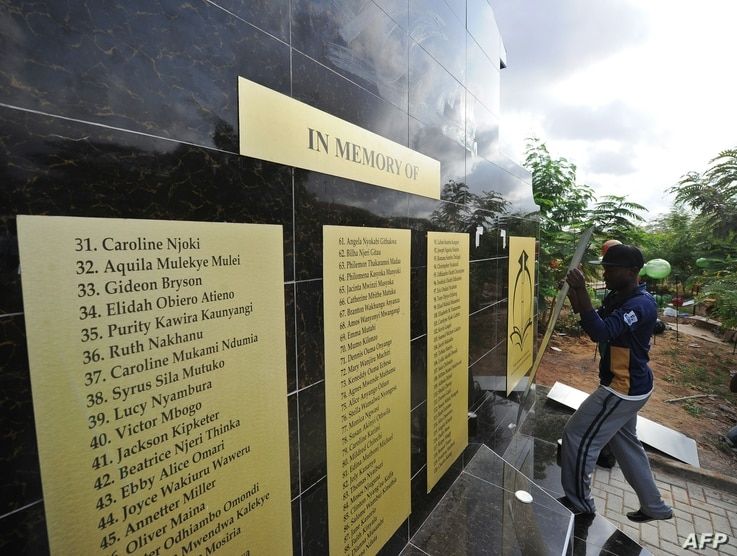 Workers mount a plaque as they work on the memorial for the victims of last year's terrorist attack that killed 148 people at the campus of Garissa University College, on April 2, 2016 in Garissa, ahead of the inaugural Garissa marathon.