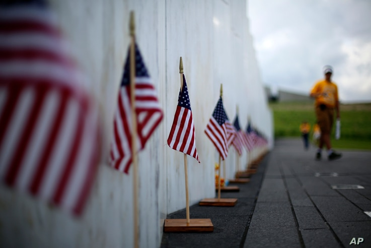 FILE - A visitor to the Flight 93 National Memorial pauses at the Wall of Names containing the names of the 40 passengers and crew of United Flight 93 that were killed in this field on Sept. 11, 2001, nears Shanksville, Pennsylvania, May 31, 2018.