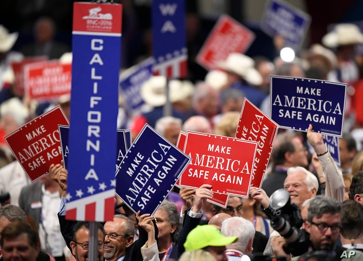 Signs are passed out to delegates during the evening session of the opening day of the Republican National Convention in Cleveland, July 18, 2016.