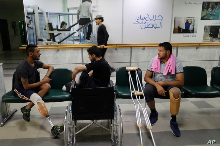 Syrian soldiers who lost their legs while fighting in Syria's war, attend a physical therapy session at the Ahmad Hamish Martyr hospital, in Damascus, Syria, Oct. 7, 2018.