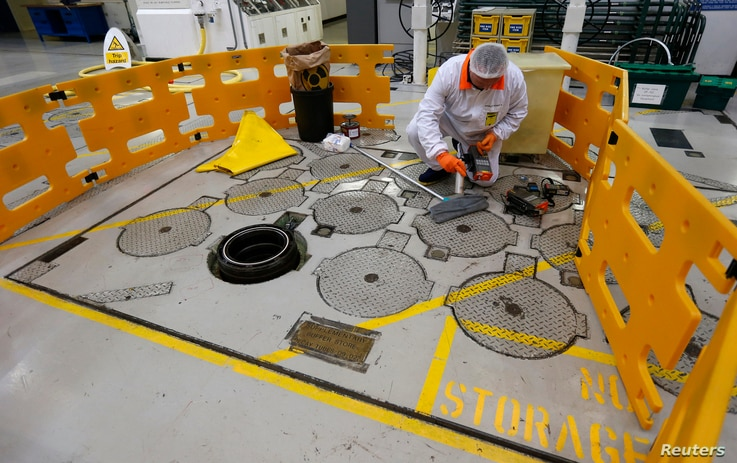An environmental safety monitor carries out contamination checks in the charge hall inside EDF Energy's Hinkley Point B nuclear power station in Bridgwater, southwest England, December 13, 2012. Chinese companies will be allowed to take stakes in Bri...