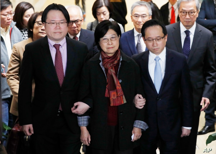 Selina Tsang, center, wife of former Hong Kong leader Donald Tsang, is accompanied by her two sons, Simon Tsang Hing-yin, left, and Thomas Tsang Hing-shun, to walk out of the High Court in Hong Kong, Feb. 22, 2017.