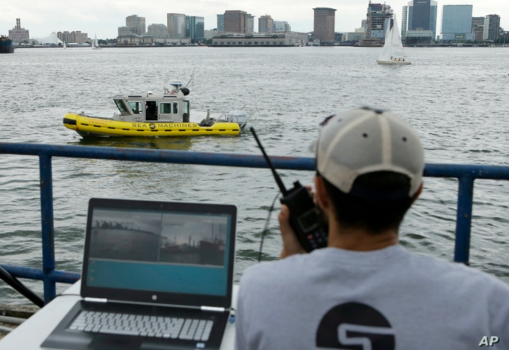 Computer scientist Mohamed Saad Ibn Seddik, of Sea Machines Robotics, uses a laptop to guide a boat outfitted with sensors and self-navigating software and capable of autonomous navigation in Boston Harbor, Aug. 15, 2017. The boat still needs human o...