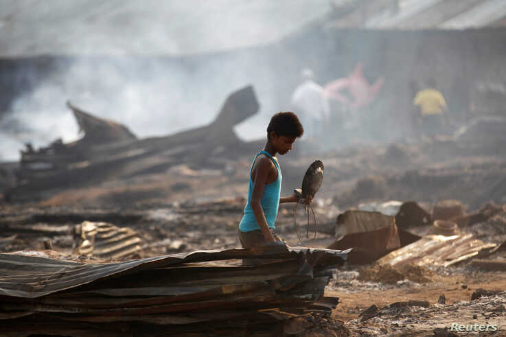 A boy searches for useful items among the ashes of burnt down dwellings after a fire destroyed shelters at a camp for internally displaced Rohingya Muslims in Myanmar's western Rakhine State near Sittwe, May 3, 2016.