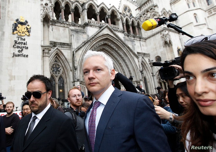 FILE - WikiLeaks founder Julian Assange leaves the High Court, with British lawyer Amal Alamuddin (R), in London, July 13, 2011.