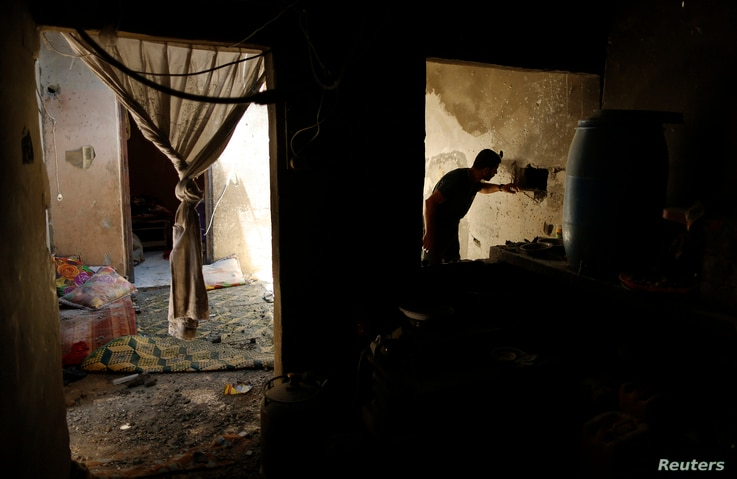 A Palestinian man inspects a house which police said was damaged in Israeli shelling on Thursday that killed two boys and a man from Nutaiz family, in Gaza City ,July 18, 2014.