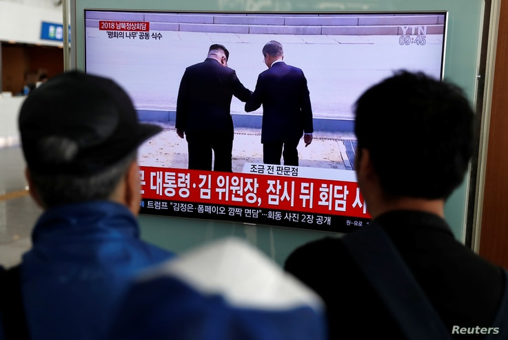 People watch a TV showing a live broadcast of the inter-Korean summit, at a railway station in Seoul, South Korea, April 27, 2018.