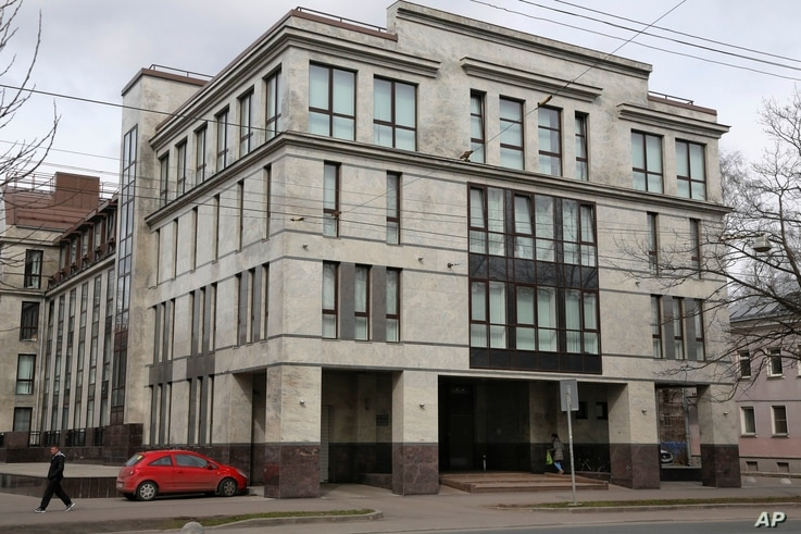 "FILE - In this picture taken April 19, 2015,  a women enters the four-story building known as the ""troll factory""  in St. Petersburg, Russia. The ""troll factory"" is where hundreds of young Russians work around the clock writing blogs and posting ..."