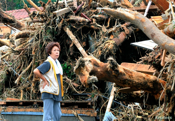 A woman reacts in front of collapsed houses following a landslide caused by Typhoon Wipha on Izu Oshima island, south of Tokyo, in this photo taken by Kyodo, Oct. 16, 2013.