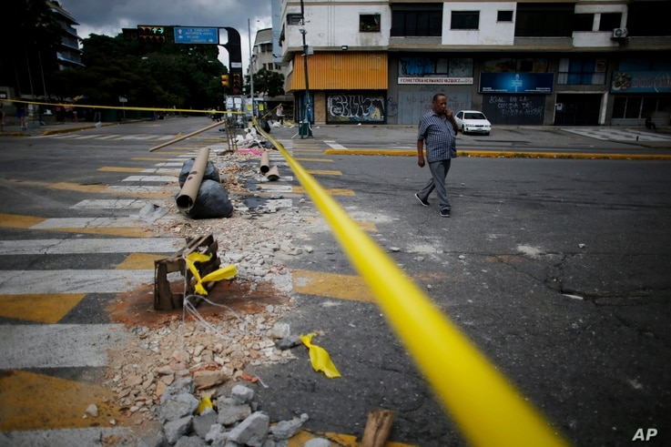 A pedestrian walks past a barricade set up by anti-government demonstrators on the second day of a 48-hour general strike in protest of government plans to rewrite the constitution, in Caracas, Venezuela, July 27, 2017.