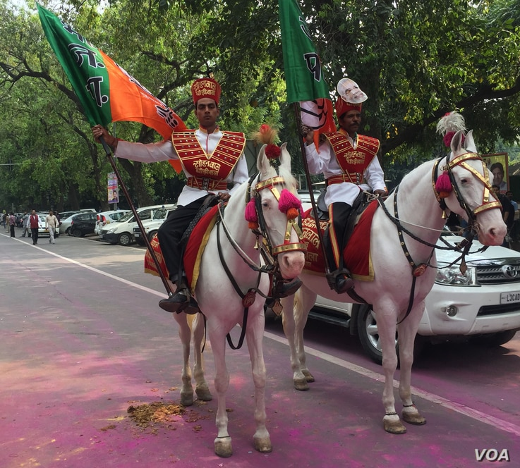 Men on horseback celebrate outside BJP offices in New Delhi, India, March 11, 2017. (A. Pasricha/VOA)