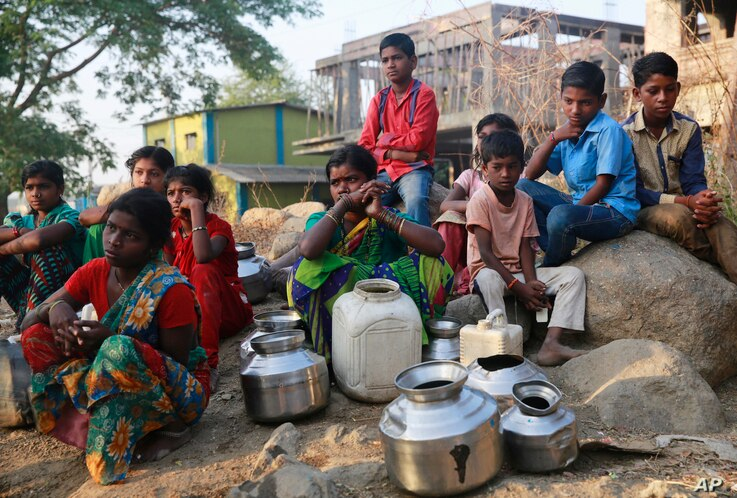 FILE - People wait to fill their vessels with water at a communal tap in Kukse Borivali, 85 kilometers (53 miles) northeast of Mumbai, India, April 12, 2016. Decades of groundwater abuse, populist water policies and poor monsoons have turned vast swa...