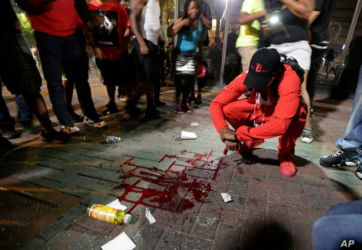 A man squats near a pool of blood after a man was injured during a protest of Tuesday's fatal police shooting of Keith Lamont Scott in Charlotte, N.C., Sept. 21, 2016.