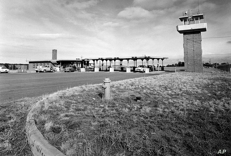 FILE - This Feb. 25, 1955 file photo shows the main gate to the Los Alamos National Laboratory, in New Mexico, where scientists developed and tested the first atomic weapon.