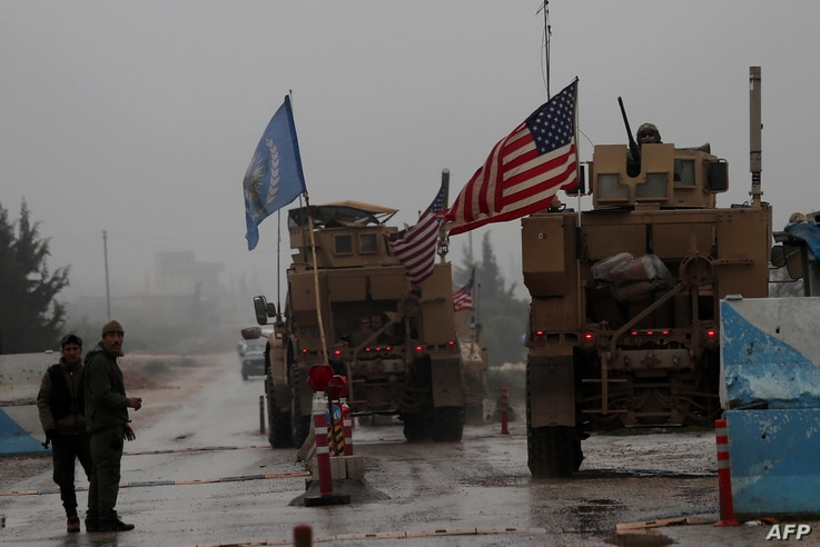A line of US military vehicles drive through a checkpoint of the Internal Security Forces in Manbij as they head to their base on the outskirts of the northern Syrian city on December 30, 2018.