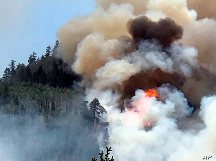 In this June 7, 2018 photo provided by Inciweb flames and smoke billow skyward as a wildfire burns near Durango, Colorado.