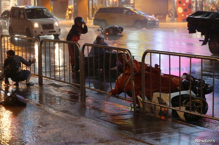 A man and motorcyclist fall as Typhoon Nesat hits Taipei, Taiwan, July 29, 2017.