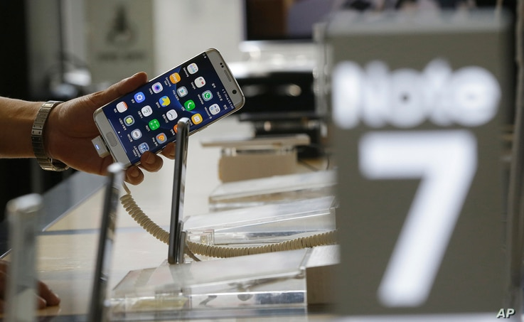A customer holds a Samsung Electronics Galaxy Note 7 smartphone at the headquarters of South Korean mobile carrier KT in Seoul, South Korea, Friday, Sept. 2, 2016.