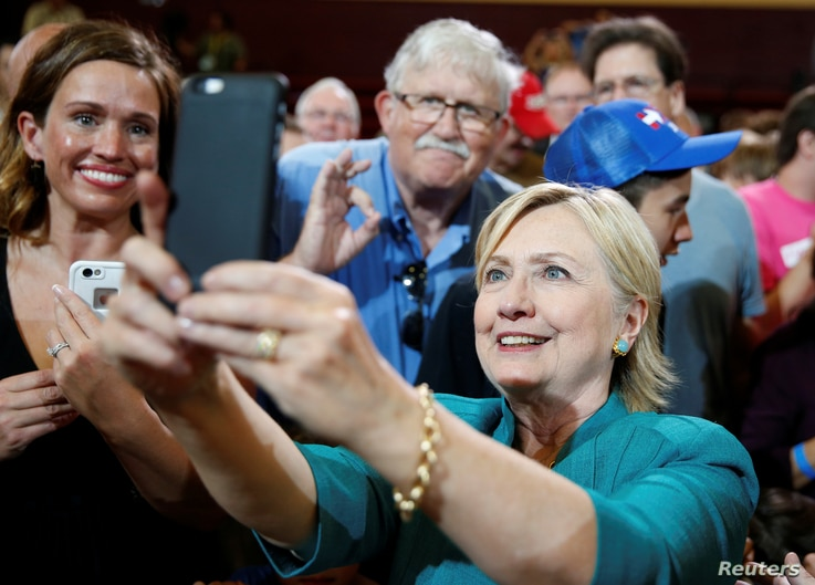U.S. Democratic presidential nominee Hillary Clinton takes a selfie with supporters following a rally at Lincoln High School in Des Moines, Iowa, Aug. 10, 2016.