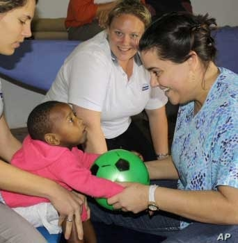 Zithulele physiotherapists Laura Grobicki (left) and Stephanie Benn (right) play with a young patient with cerebral palsy, as occupational therapist Shannon Morgan looks on. Compassion is the hospital's mantra