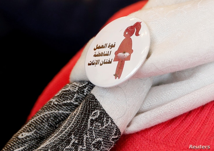 """FILE - A badge reads """"The power of labor aginst FGM"""" is seen on a volunteer during a conference on International Day of Zero Tolerance for Female Genital Mutilation in Cairo, Egypt, Feb. 6, 2018."""