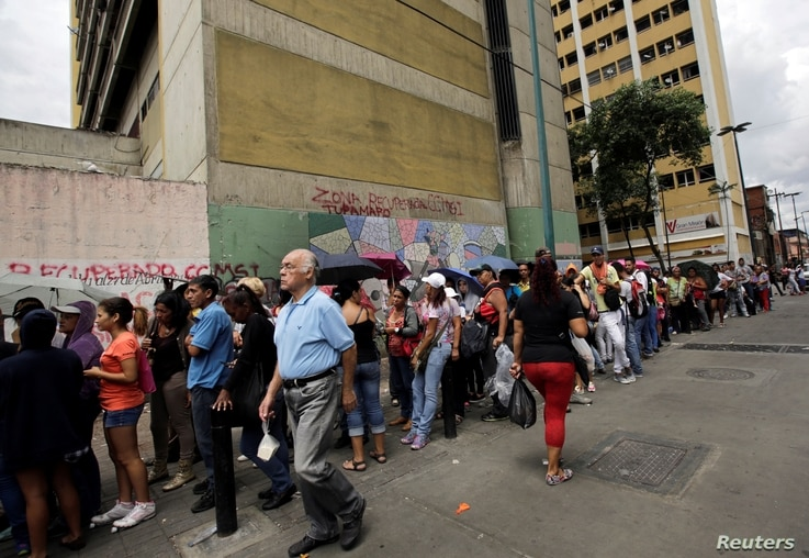 People stand in line as they wait to buy staple items and basic food along a sidewalk of a supermarket in Caracas, Venezuela September 8, 2016. REUTERS/Henry Romero - RTX2OPRW