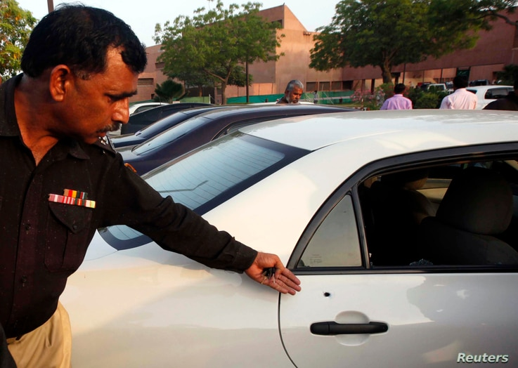 A policeman shows the media a bullet hole in the door of a car which belongs to journalist Hamid Mir, at a local hospital in Karachi, Apr. 19, 2014.