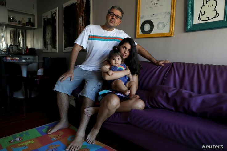 FILE - Tatiana Barcellos, 37, a civil servant for the Federal Prosecutor's Office, her eight-month-old daughter Alice, and her husband Marcelo Valenca, 39, a teacher at a navy school, pose for a photograph on the day Tatiana went back to work, at the...