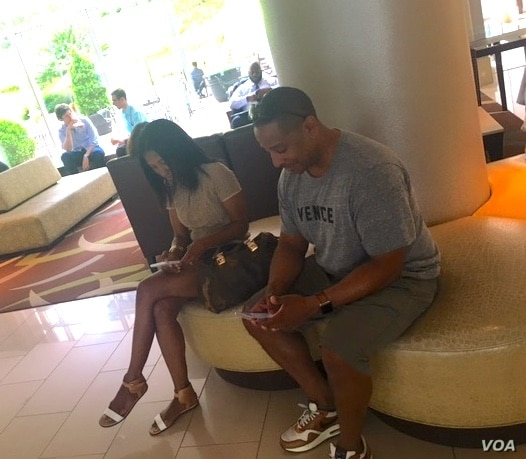 A couple on vacation sit side by side in a hotel in Washington DC, but are busy reading their smartphones. (VOA/CMaddux)