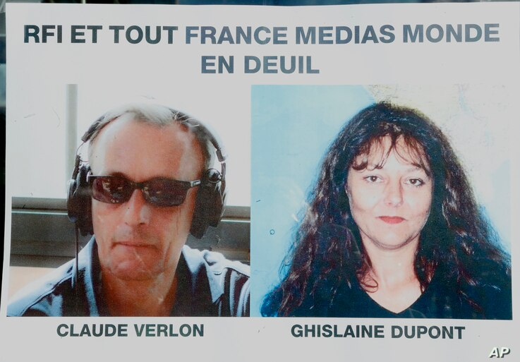 """Pictures of French RFI journalists, Ghislaine Dupont, right, and Claude Verlon on a poster headed """"RFI and all France Media World in Mourning"""" displayed in a window in Paris, Nov. 3, 2013."""