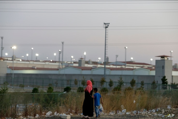 FILE - A woman and a boy walk outside a high security prison complex in Silivri, about 80 kilometers (50 miles) west of Istanbul, Aug. 17, 2016.