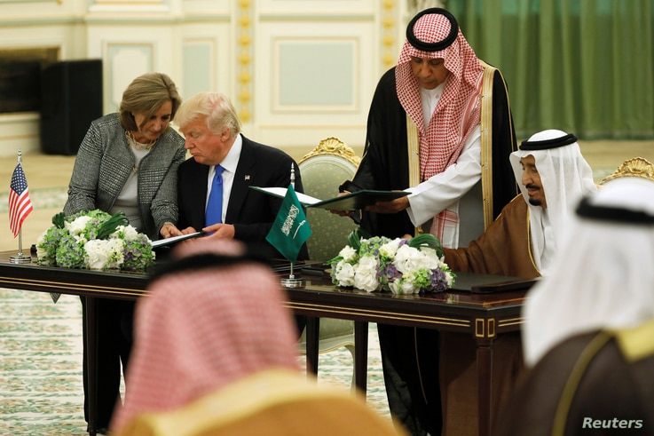 Saudi Arabia's King Salman bin Abdulaziz Al Saud (right) and U.S. President Donald Trump sign a joint security agreement at the Royal Court in Riyadh, Saudi Arabia, May 20, 2017.