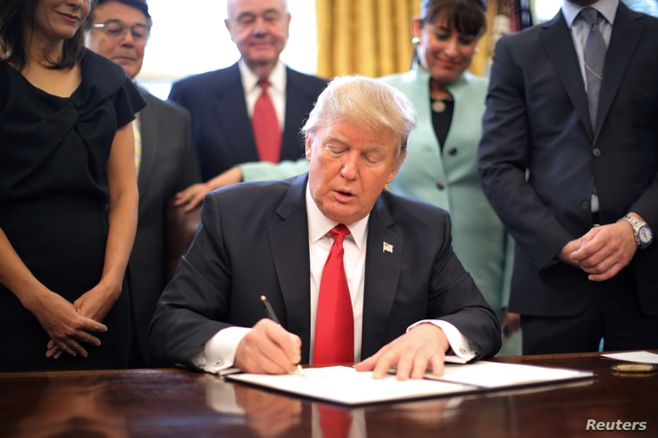 U.S. President Donald Trump signs an executive order cutting regulations, accompanied by small business leaders at the Oval Office of the White House in Washington, Jan. 30, 2017.