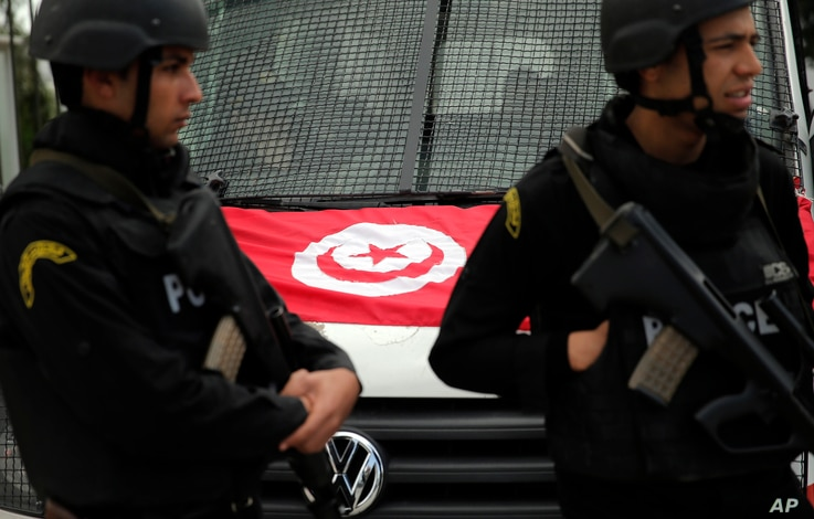 FILE - A Tunisian national flag is seen on a police vehicle as policemen stand guard following an attack by gunmen in Tunis, Tunisia, March 20, 2015.