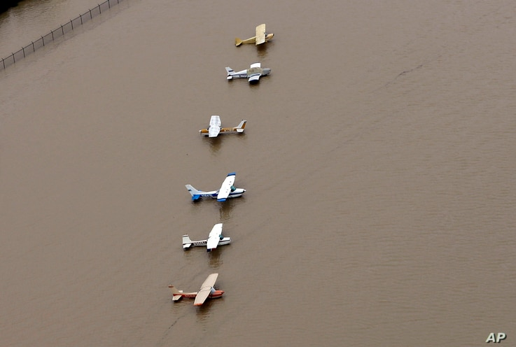 Airplanes sit at a flooded airport near the Addicks Reservoir as floodwaters from Tropical Storm Harvey rise, Aug. 29, 2017, in Houston.