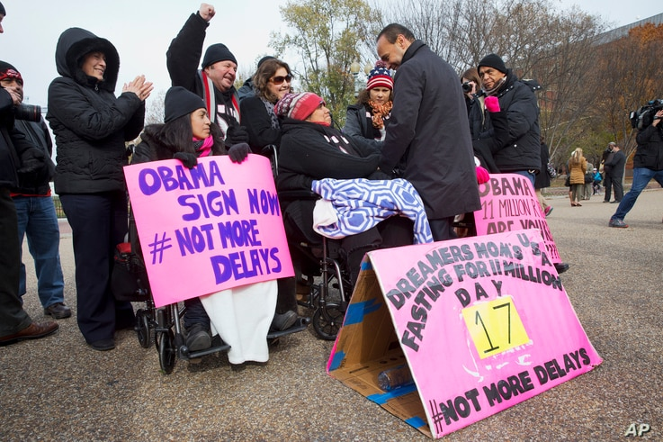 Rep. Luis Gutierrez, D-Ill.,  right, speaks with Lenka Mendoza of Dumfries, Va., who is originally from Peru, during a rally in front of the White House in support of executive action addressing immigration reform, Nov. 19, 2014.