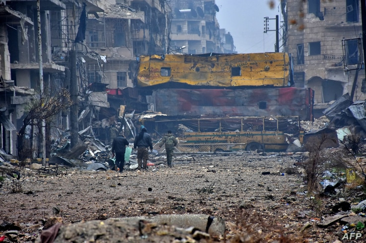 Syrian pro-government forces walk in Aleppo's Bustan al-Qasr neighborhood after they captured the area in the eastern part of the war torn city, Dec. 13, 2016.