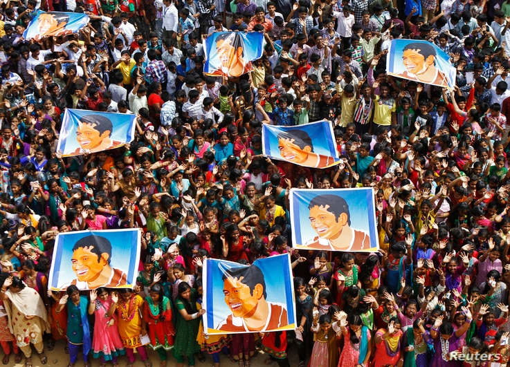 School children wave as they hold posters of Indian cricketer Sachin Tendulkar at an event to honour him inside a school in the southern Indian city of Chennai November 14, 2013.