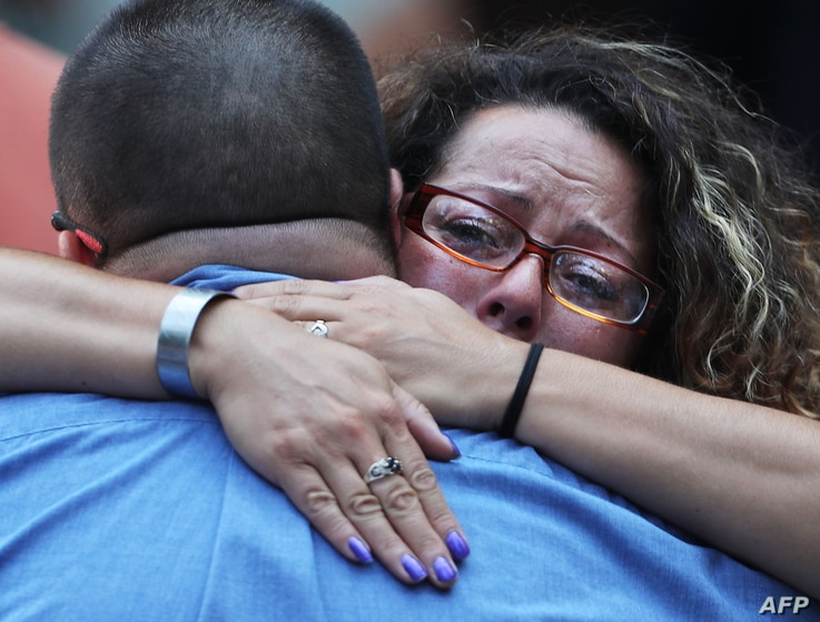 A woman hugs a man during a commemoration ceremony for the victims of the September 11 terrorist attacks at the National September 11 Memorial and Museum in New York City, Sept. 11, 2016.