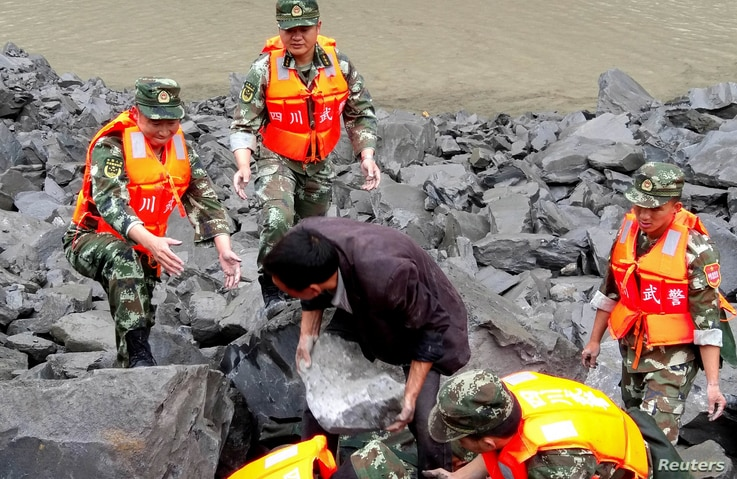 Rescue personnel work at the site of a landslide that destroyed more than 60 households, where more than 100 people are feared to be buried, according to local media reports, in Xinmo Village, China, June 24, 2017.