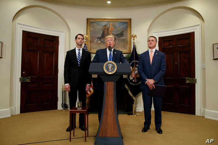 President Donald Trump, flanked by Sen. Tom Cotton, R- Ark., left, and Sen. David Perdue, R-Ga., speaks in the Roosevelt Room of the White House in Washington, Aug. 2, 2017, during the unveiling of legislation that would place new limits on legal imm...