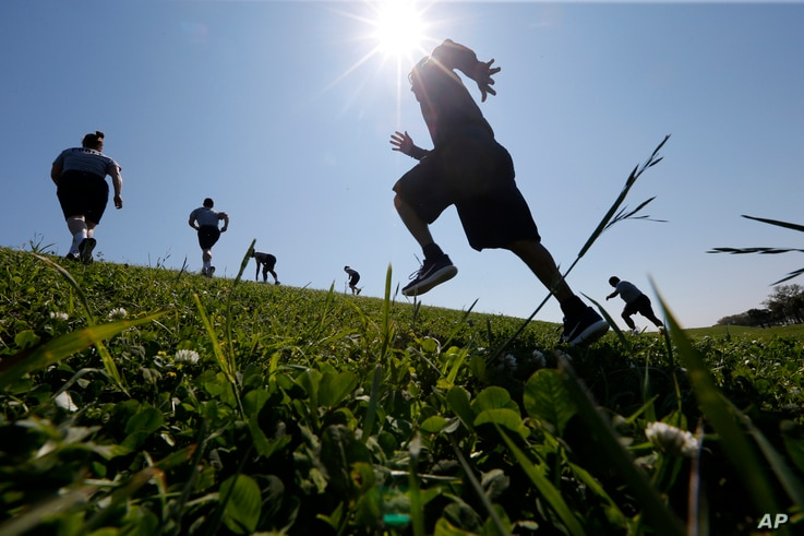 Recruits and instructors from the New Orleans Police Department academy run through drills on a levee along Lake Pontchartain in New Orleans, March 15, 2017. Temperatures were in the 60s.
