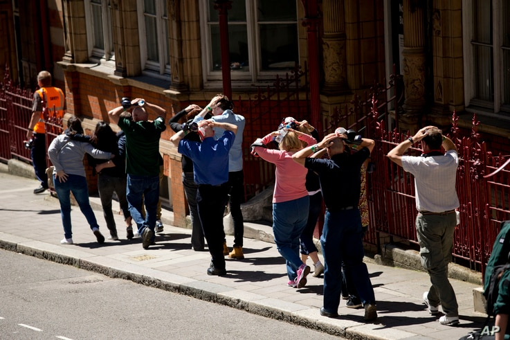 During a training exercise for London's emergency services, people walk away with their hands on their heads from the disused Aldwych underground train station in London, June 30, 2015.